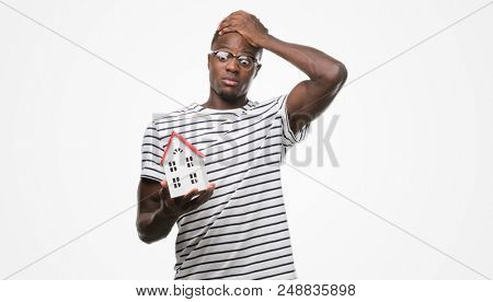 Young african american man holding house stressed with hand on head, shocked with shame and surprise face, angry and frustrated. Fear and upset for mistake.