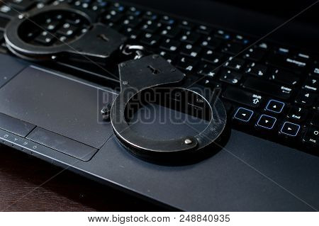 Steel Police Handcuffs Lying On Keyboard. Concept Of Internet Crime, Hacking, Cyber Crimes And Virtu