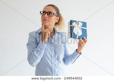 Pensive Attractive Woman Holding Gift And Looking Aside. Serious Young Lady In Glasses Thinking Of P
