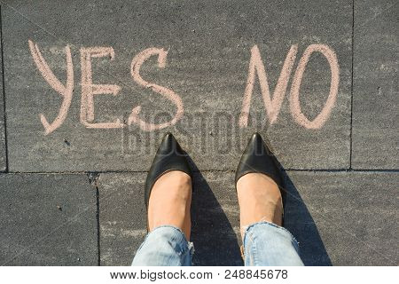 Woman Before The Choice Yes Or No. View From Above, Female Feet With Text Yes No Written On Grey Sid