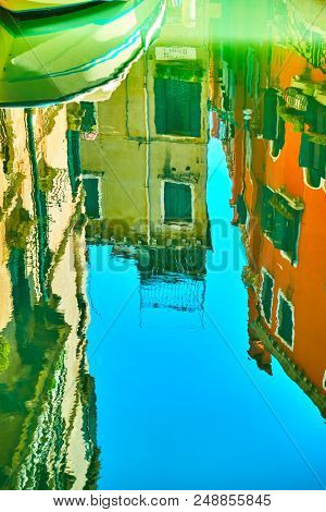 Venetian mirror - Houses, boat and blue sky reflect in the water of canal. Venice in water reflections