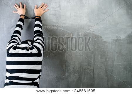 Rear View Of Unidentified Prisoner In Prison Stripped Uniform Standing Near The Wall In The Dark Int