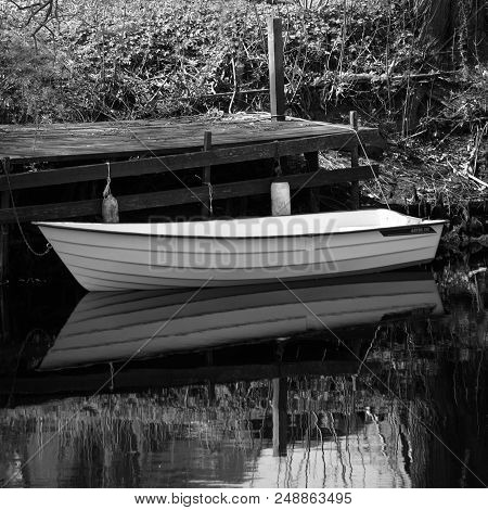 Small Boat Moored To Old Wood Bridge.
