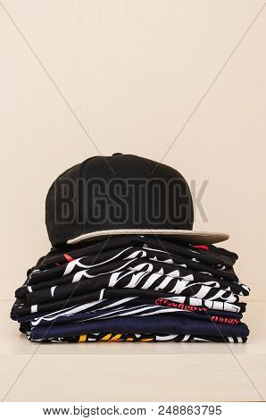 Pile Of Brand New T-shirts, Dark Tones, With Print And A Black Cap Over The Pile.