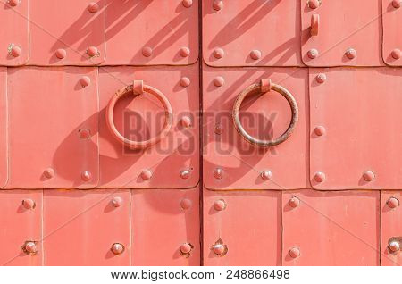 Metal Red Aged Textured Door With Rings Door Handles And Metal Rivets. Metal Architecture Background
