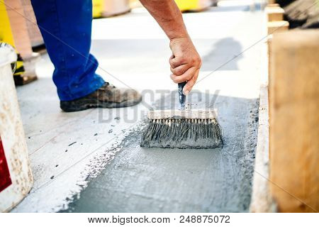 Construction Worker Using Brush And Primer For Hydroisolating And Waterproofing House