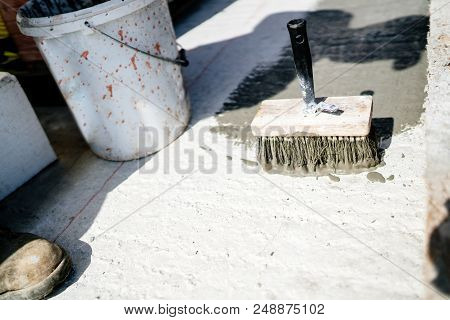 Industrial Tools On Construction Site, Painters Brush With Waterproof Sealant On Concrete Surface