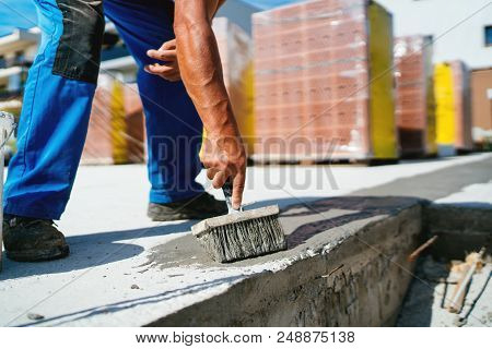 Industrial Worker On Construction Site Laying Sealant For Waterproofing Concrete On Construction Sit