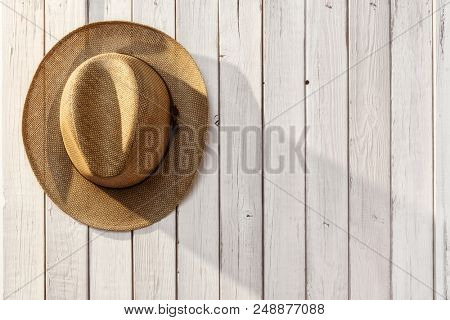 Top view of straw hat on the wooden background