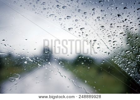 Wet Windshield Of The Bus While Driving On A Tourist Route. Drops Of Rain On The Car Glass. The Road