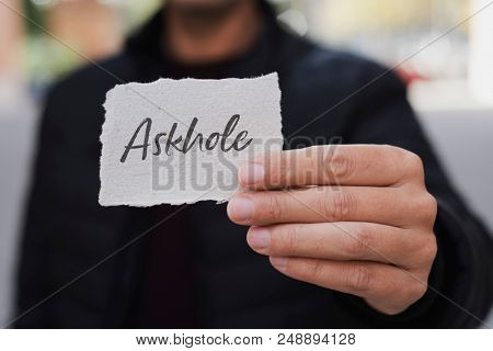 closeup of a young caucasian man, on the street, showing a piece of paper with the word askhole written in it, for the person who constantly asks for advice and does the opposite poster
