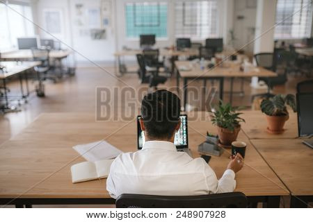 Rearview Of A Businessman Sitting At His Desk Going Over Paperwork And Working On A Laptop In A Mode