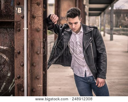 One Handsome Young Man In Urban Setting In European City, Standing, Wearing Black Leather Jacket And