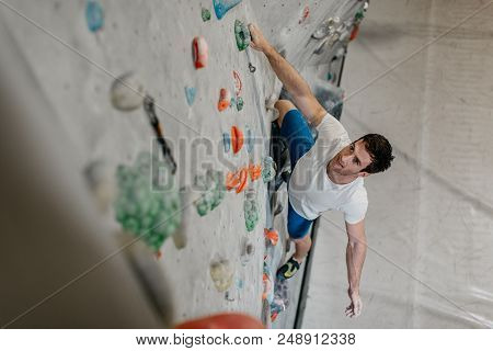 High Angle View Of A Boulderer Climbing Up A Bouldering Wall. Male Climber Making His Way Up An Arti