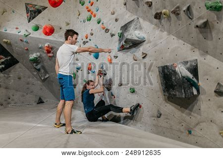 Man And Woman Climbing In An Indoor Bouldering Gym. Bouldering Instructor Showing A Way To A Female