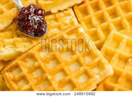 Close-up Of Homemade Brown Waffles With Marmelade On A Spoon. View To Stacked Wafles With Jam. Baker