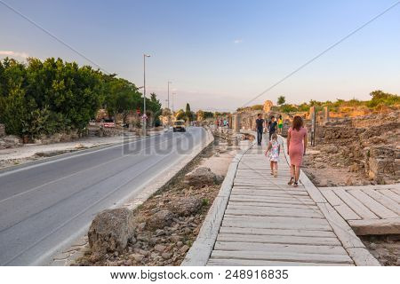 Side, Turkey - June 8, 2018: People on the main road to Side town at sunset, Turkey. Side  is an ancient Greek city on the southern Mediterranean coast of Turkey.