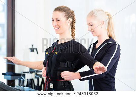 Female coach dress woman in ems electro muscular stimulation costume  poster