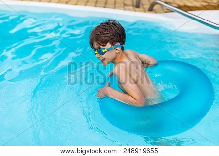Side View Of Happy Boy In Swimming Glasses With Inflatable Ring Swimming In Swimming Pool On Summer