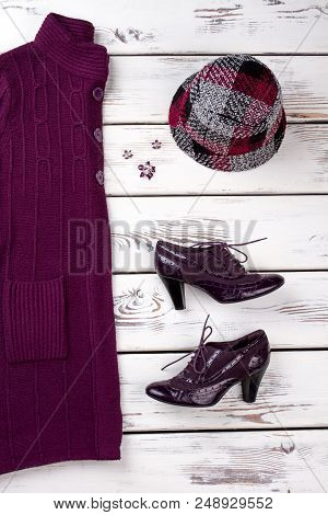 Concept of winter garment. Hight heel shiny shoes with shoelaces, hat and coat. poster