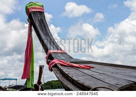 Satin Fabric Tie On The Prow Of Wooden Boat At Cloudscape Background.