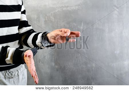 Unidentified Hands Of Prisoner In Prison Stripped Uniform Standing In Handcuffs And Holding A Key In