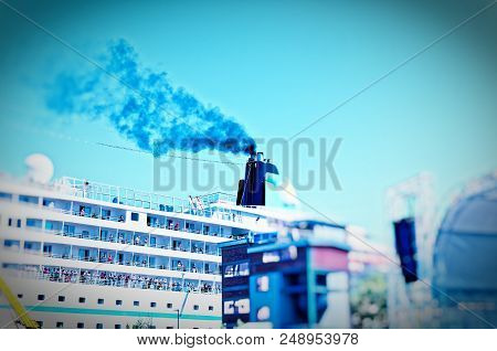 Ship That Lies In A Harbor With A Clear Plume Of Smoke On The Chimney To Illustrate The Air Pollutio
