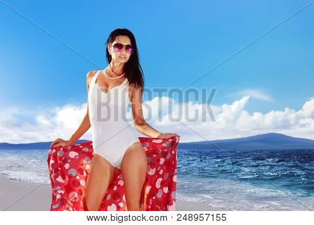 beautiful woman in a bathing suit derives pleasure on the beach during her holiday
