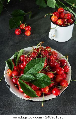 Full Bowl And Mug Of Pink Cherries With Leaves, On Dark Surface