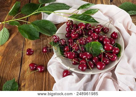 Large Ripe Cherries With Tails In Ceramic Dish, On Table With Light Cloth