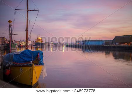 Harbour lights. Soft landscape image of river port quay at dusk. Tranquil harbor scene of quayside boats and shipping from the fishing town of Great Yarmouth, England, UK. poster