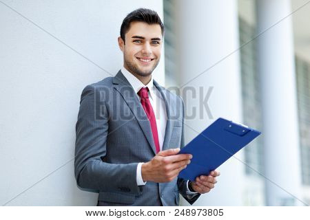 Portrait of an handsome young manager outdoor reading documents