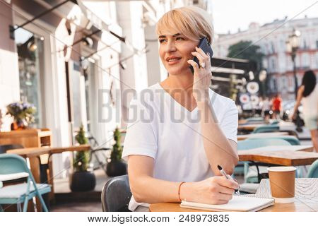 Caucasian pleased woman 30s wearing white t-shirt sitting in street cafe while writing down in notebook and speaking on mobile phone