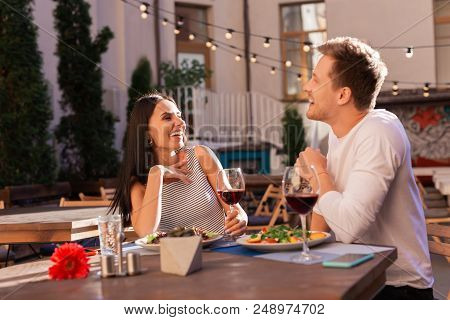 Fancy Terrace. Dark-haired Appealing Woman Laughing Out Loud With Her Handsome Man While Sitting On