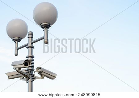 Public City Video Surveillance Cameras And Street Lamps On The Lamppost Over Sky