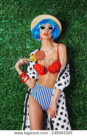 Portrait of a bright fashion model with blue hair wearing swimsuit over lawny background. Beauty, fashion concept.  Pin-up style.