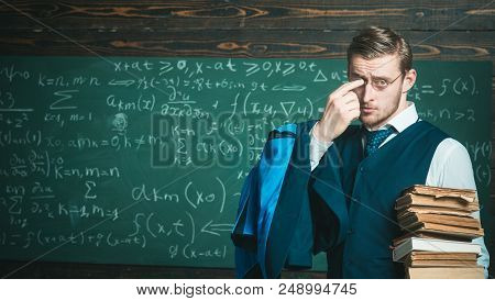 Teacher Formal Wear And Glasses Looks Smart, Chalkboard Background. Man In End Of Lesson Takes Off E