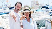 Middle age couple in marina with angry face, negative sign showing dislike with thumbs down, rejection concept poster