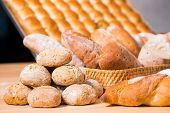 on the foreground a traditional round artisan wheat bread loaves on a table .On the background another breads. Rustic style, selective focus poster