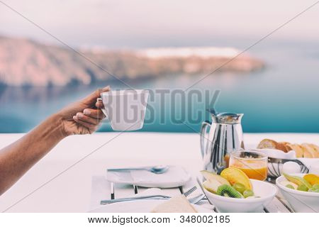 Drinking coffee cup at breakfast brunch table of cruise ship restaurant - luxury travel vacation getaway in Santorini - honeymoon destination.