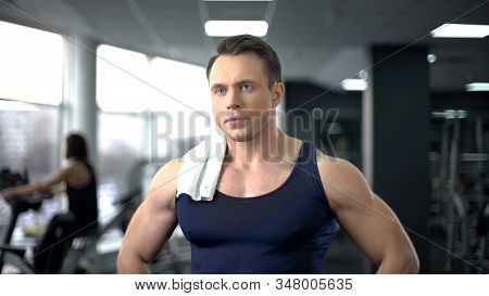 Serious Bodybuilder With Towel On Shoulder Relaxing After Hard Workout In Gym