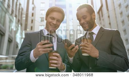 Happy Business Partners Reading Good News About Stock Market On Smartphones