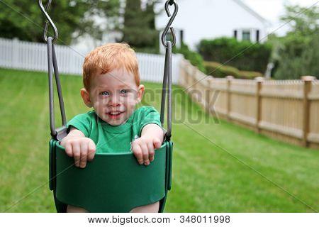 Cute toddler boy sitting on a swing