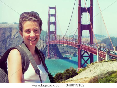 A woman hiker in front of the Golden Gate Bridge in San Francisco
