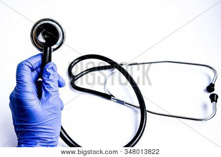 The Stethoscope In Hand In Medical Glove Medicine, Medical Concept, Diagnostic Tool - Phonendoscope