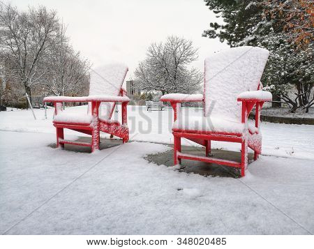 Two Red Wooden Adirondack Muskoka Chairs Covered With Snow On Winter Day In Park Outdoor. Winter Sea