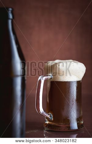 Pint Of Black Beer With Foam And Frost, On Brown Background. Cold Glass Of Beer. Summer Drink. Dark