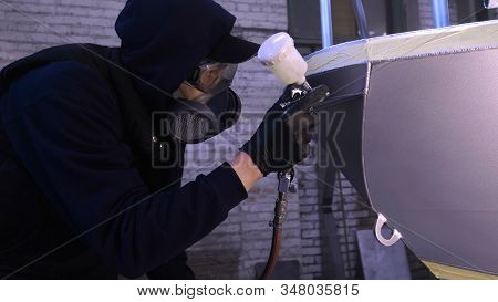 man (guy) in a garage (service) in working clothes dressed in a sweater sets up a paint gun (spray g