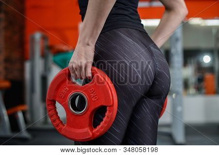 Slim, Bodybuilder Girl With Sexy Buttocks Lifts Heavy Dumbbell, Closeup. Woman With Perfect Big Butt