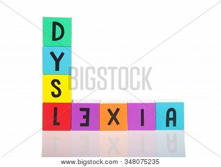Bright Colorful Wooden Toy Blocks Stacked On A Reflective Surface Spelling Dyslexia. Learning Challe